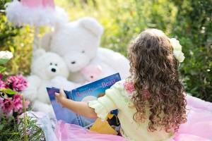 niña leyendo cuento a sus peluches